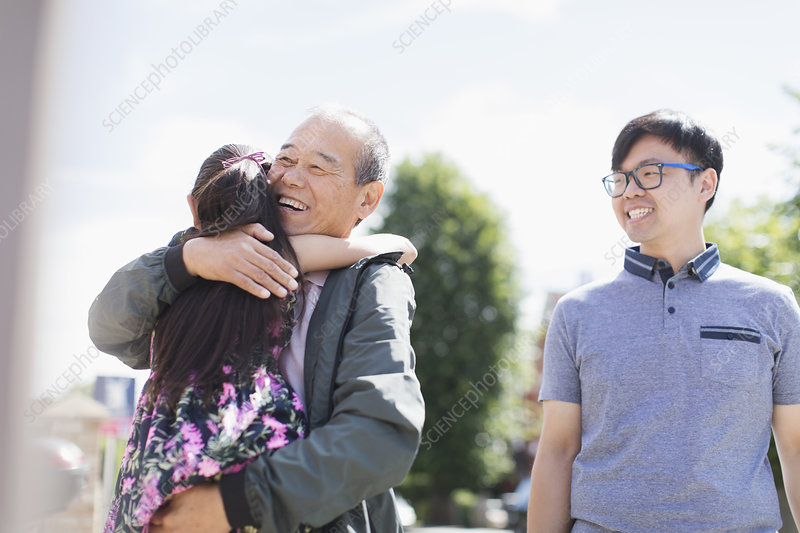 grandfather and granddaughter hugging