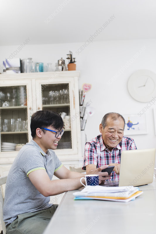 Son helping senior father paying bills at laptop