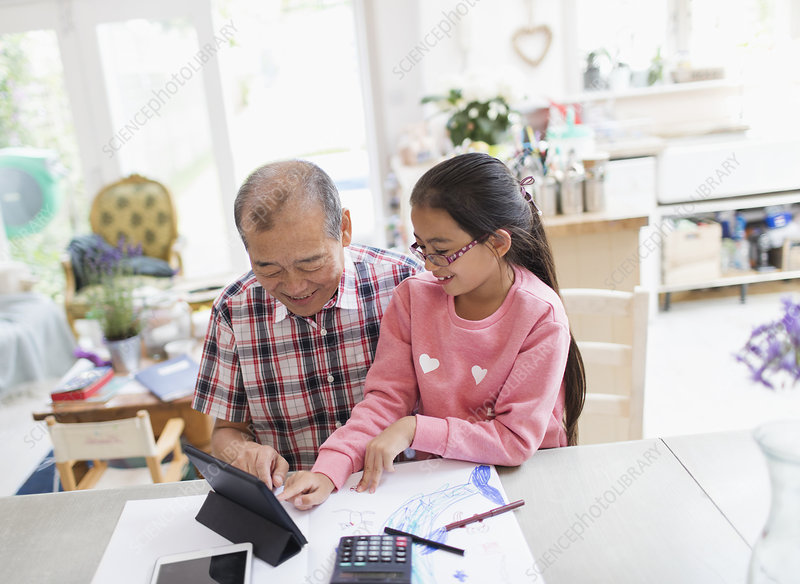 Grandfather and granddaughter using tablet