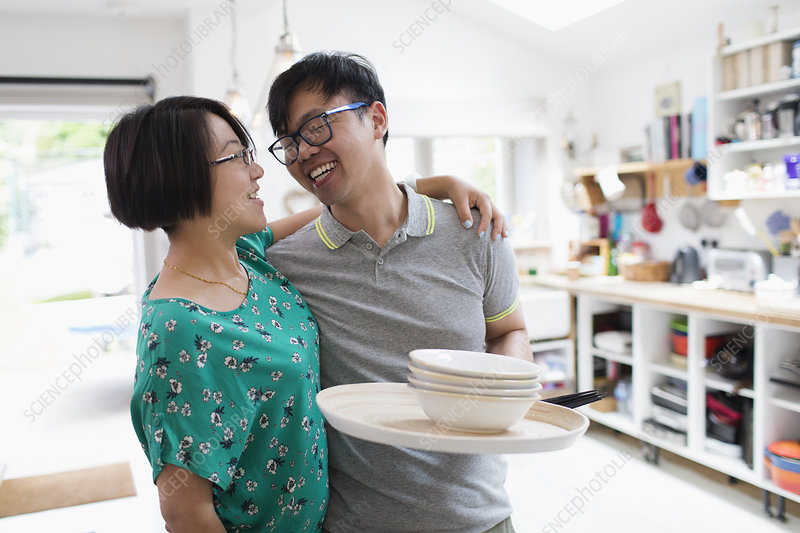 Couple hugging, doing dishes in kitchen