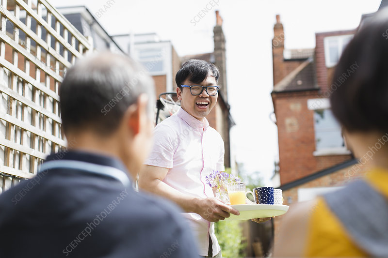 Happy man serving tea and juice to family in yard