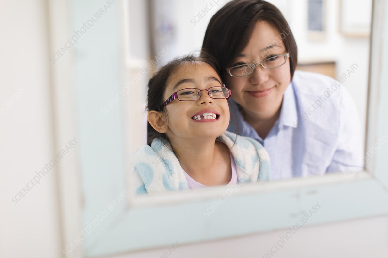 Mother watching daughter showing teeth