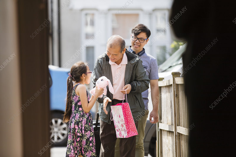 Grandfather giving granddaughter stuffed animal