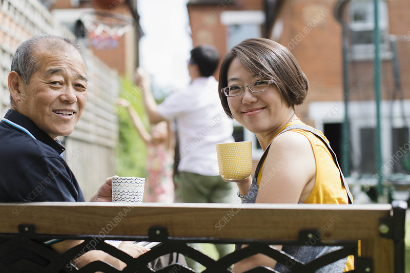 Daughter and senior father drinking tea on bench