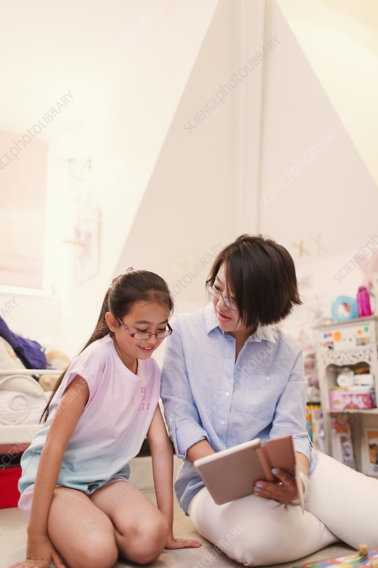 Mother and daughter using tablet in bedroom