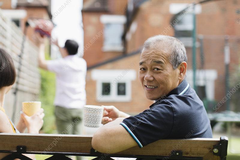 Portrait senior man drinking tea with family