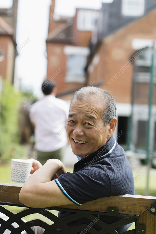 Portrait senior man drinking tea in yard