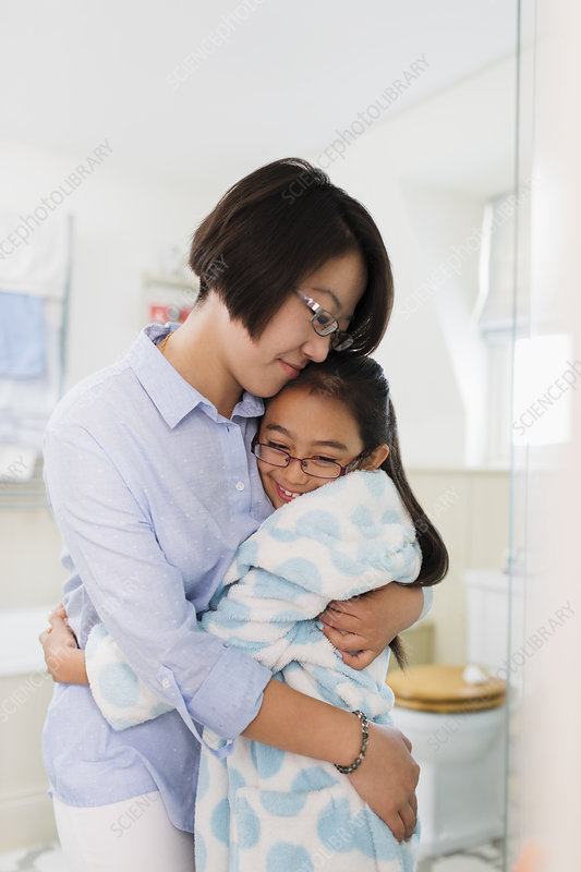 Mother and daughter hugging in bathroom