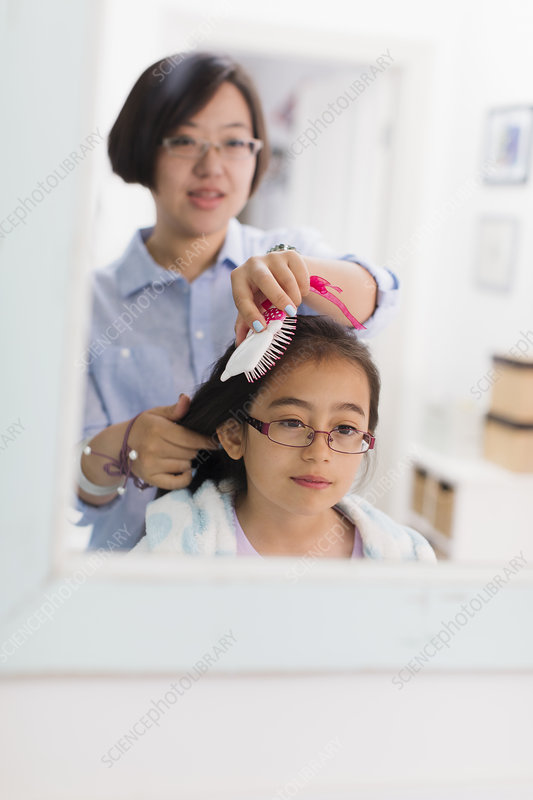 Mother brushing daughters hair in bathroom mirror