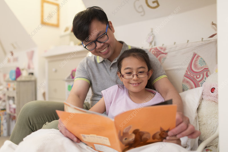Father and daughter reading book in bedroom