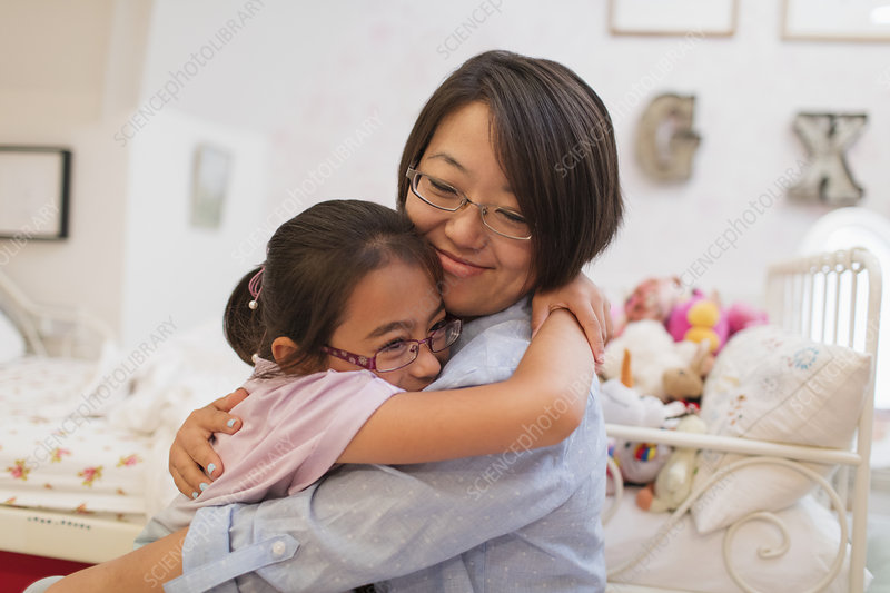 Mother and daughter hugging in bedroom