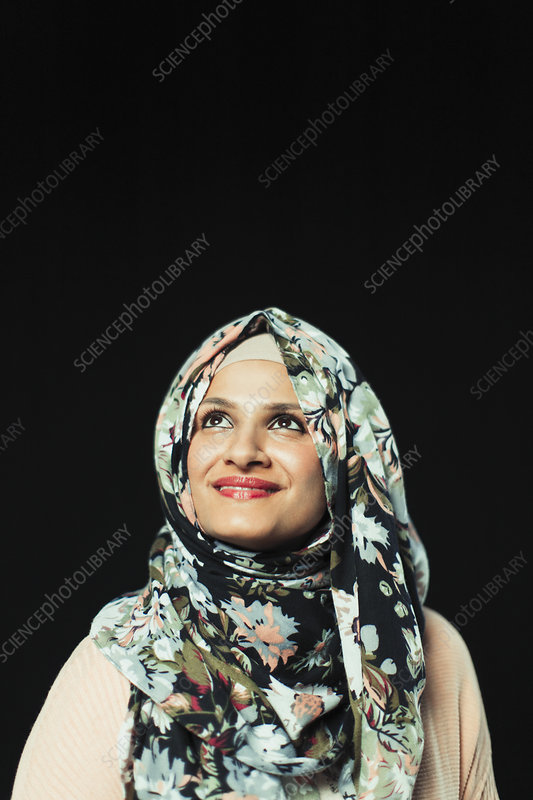 Ambitious woman in floral hijab looking up