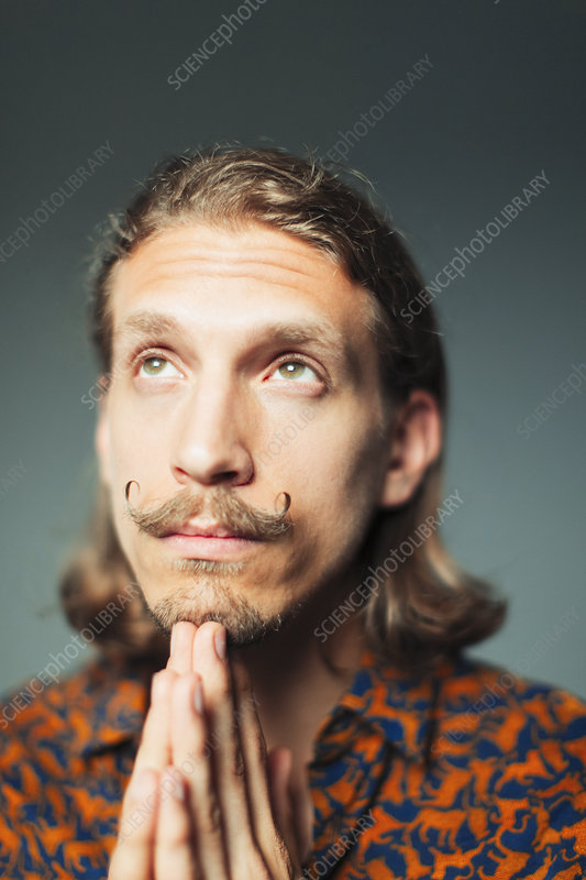 Portrait young man with handlebar moustache praying