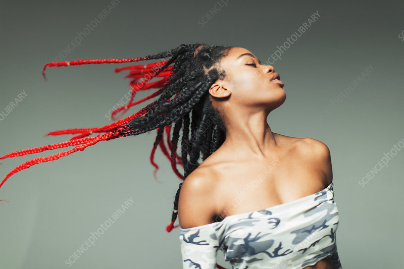 Carefree young woman flipping braids