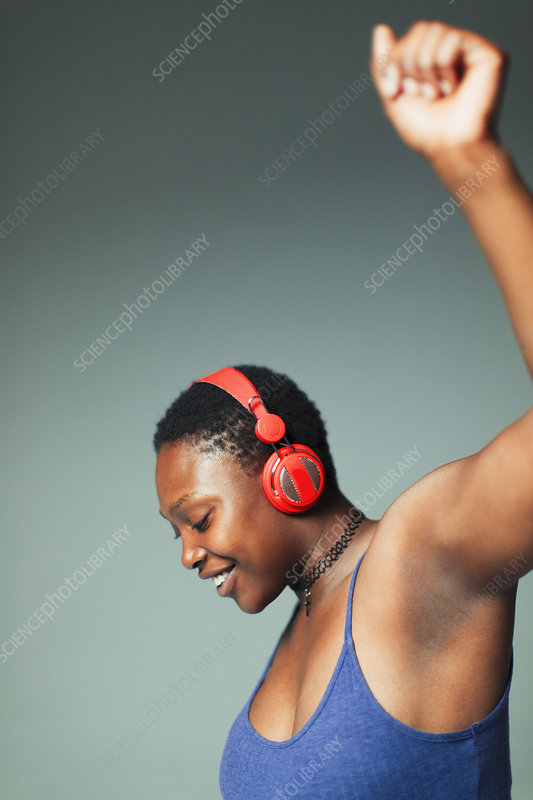 Carefree woman with headphones dancing