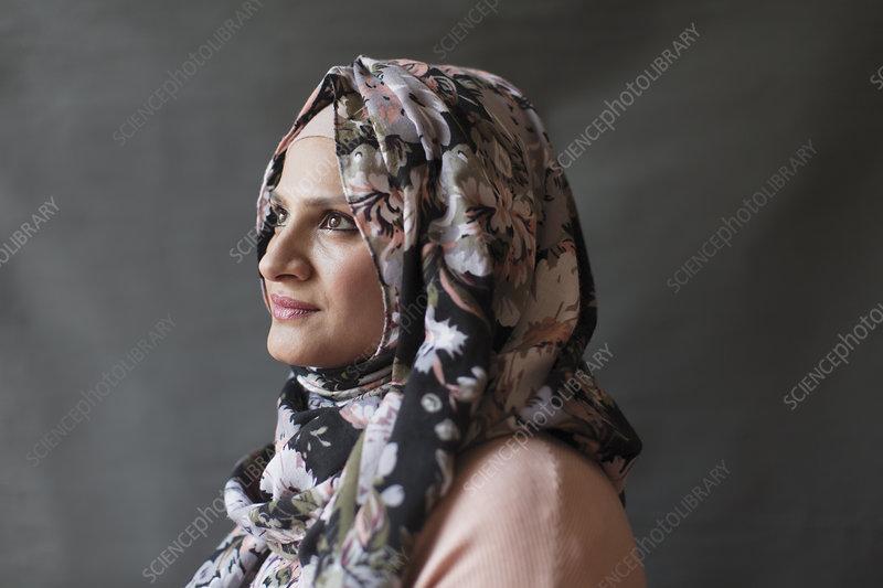 Serene, thoughtful woman wearing floral hijab