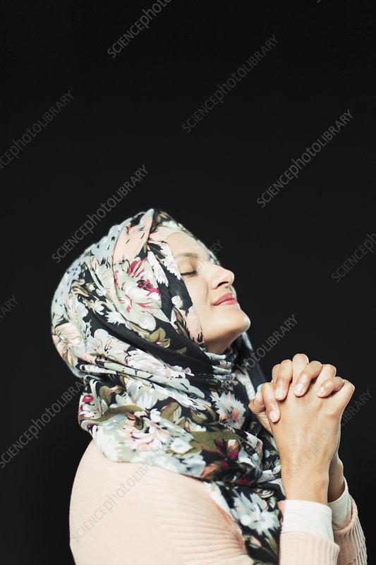 Serene woman in floral hijab praying