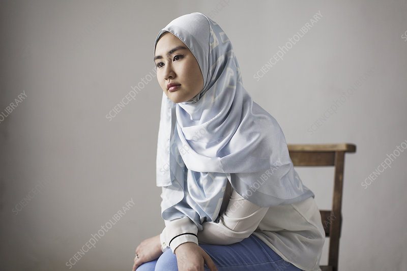 Thoughtful young woman in blue silk hijab
