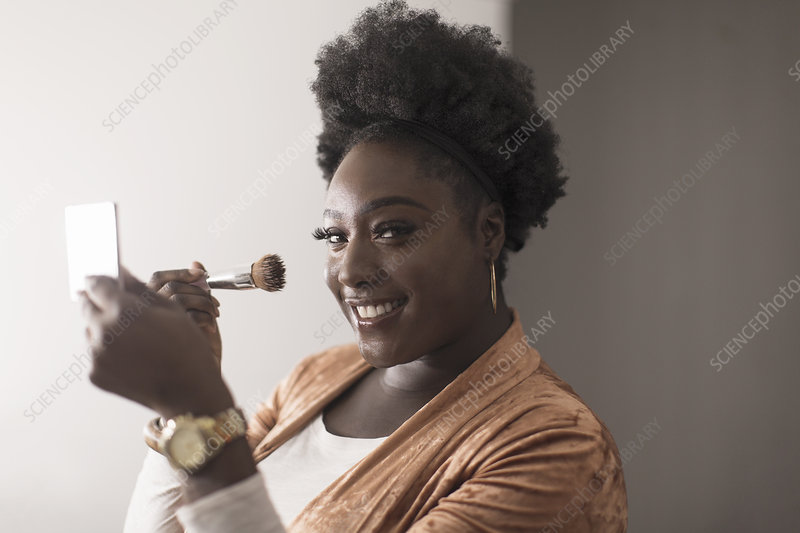 Portrait woman applying makeup in compact mirror