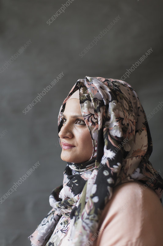 Thoughtful woman in floral hijab looking up
