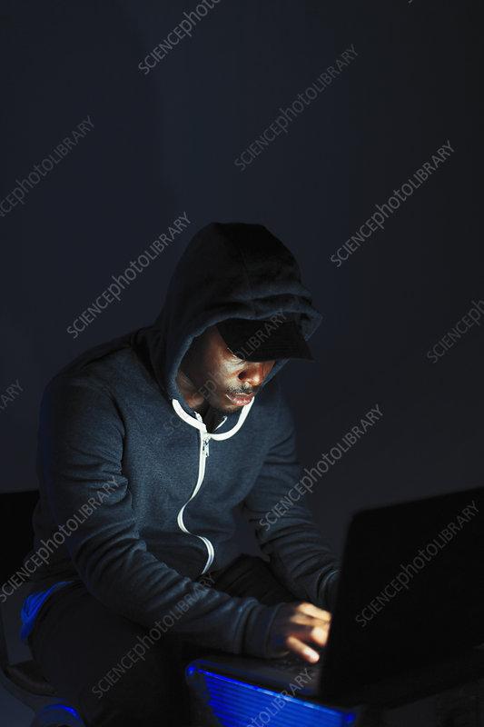 Teenage boy in hoody sitting at laptop