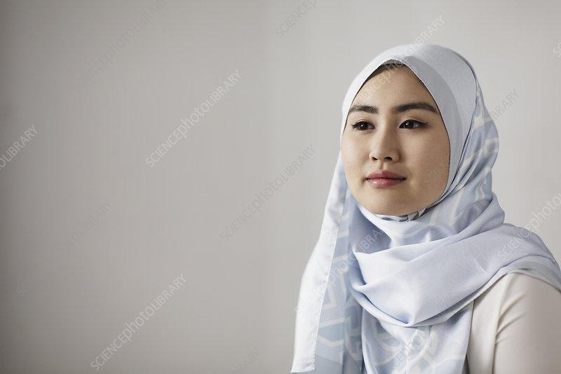 Portrait woman in blue silk hijab looking away