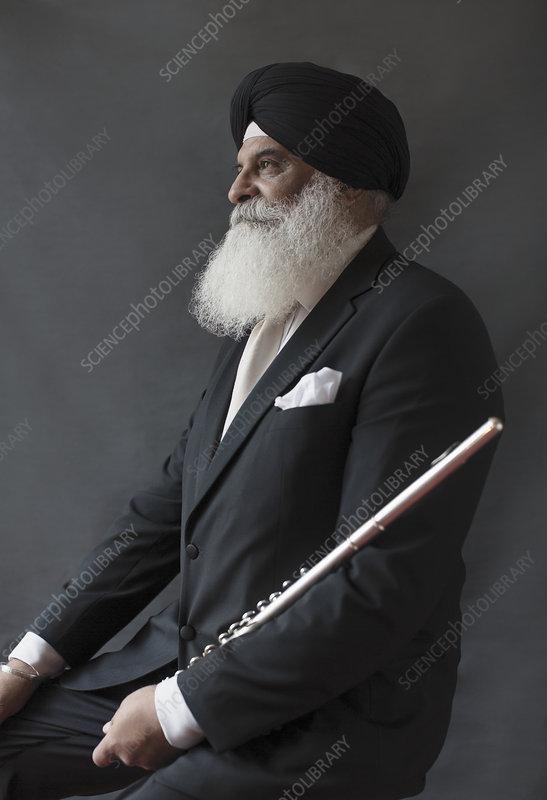 Senior man in turban holding flute