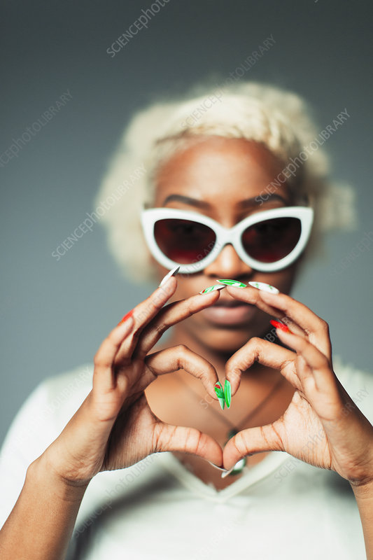 Portrait woman gesturing heart-sign with hands