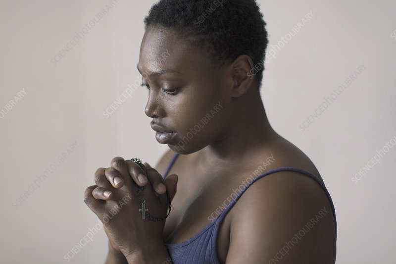 Serene woman praying with rosary