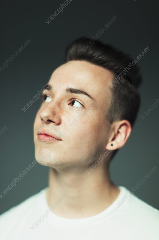 Teenage boy with freckles and earring looking up