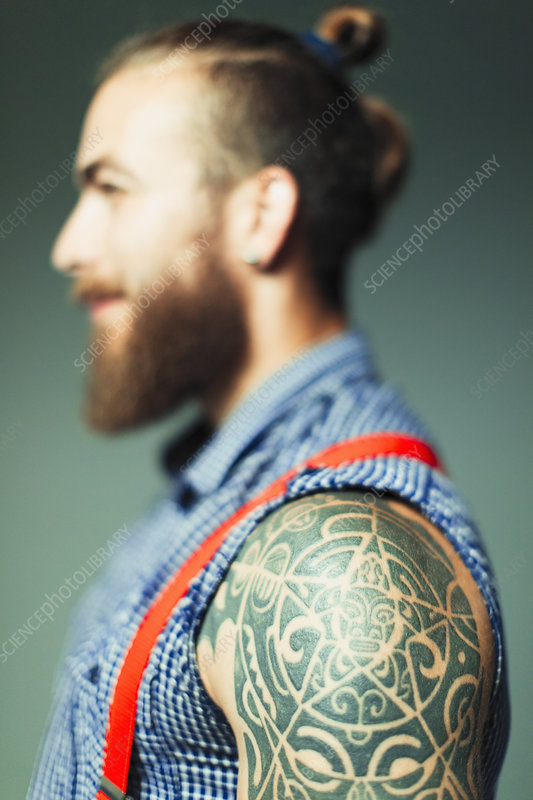 Hipster man with shoulder tattoo and beard