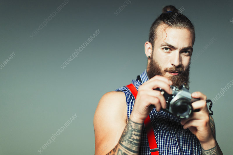 Portrait hipster man with retro camera