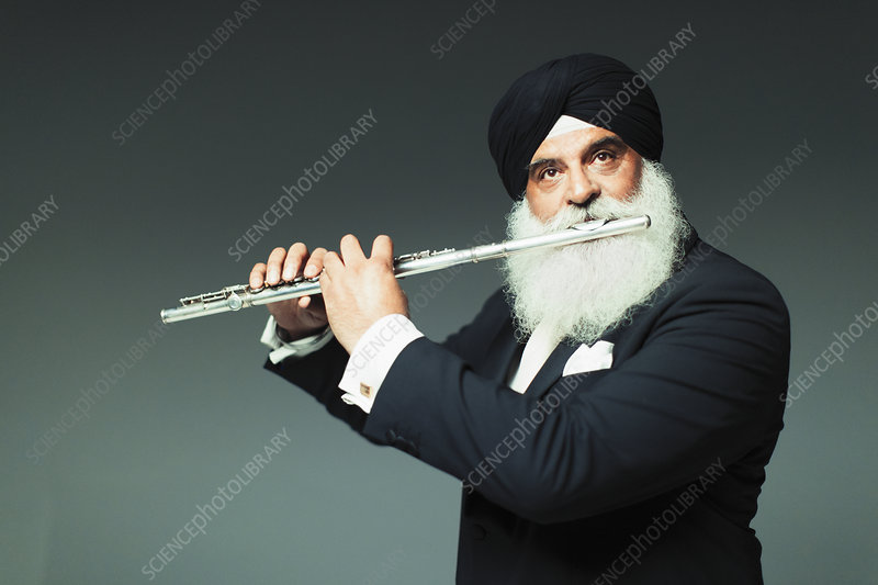 Well-dressed senior man in turban playing flute