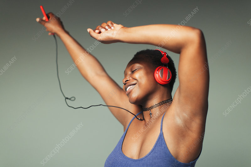 Carefree young woman with headphones dancing