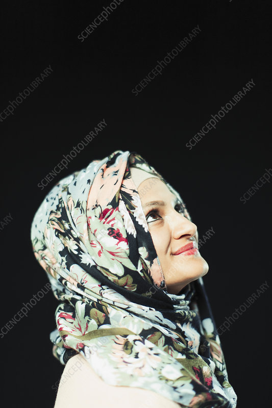 Portrait woman in floral hijab looking up