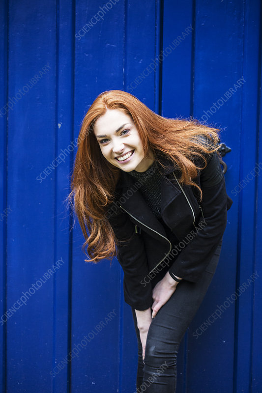 Portrait of smiling young woman in front of bright blue door