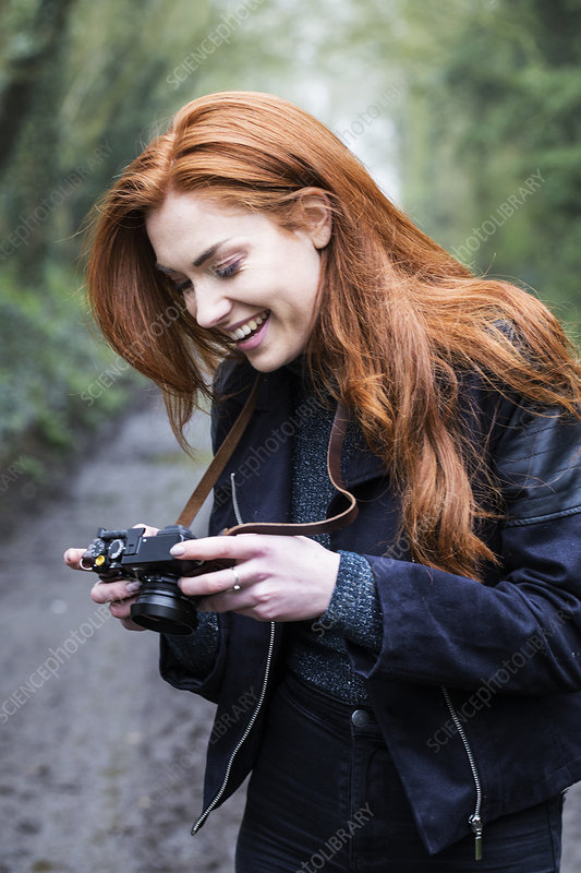 Smiling young woman taking pictures with vintage camera