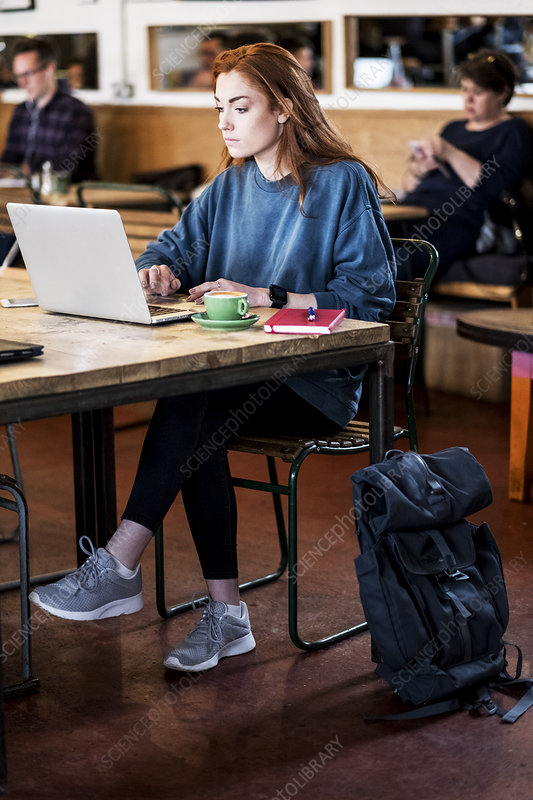 Young woman sitting at table, working on laptop computer