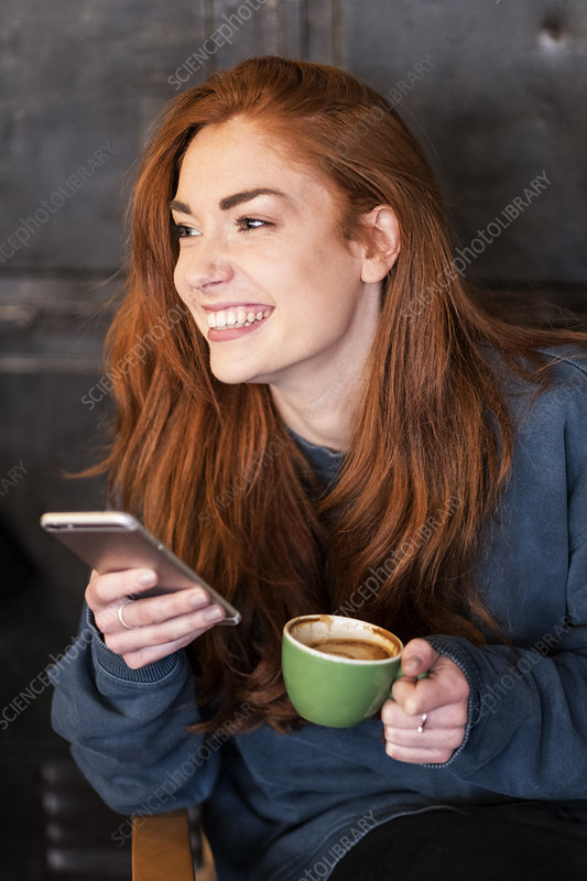 Smiling young woman seated at table, mobile phone and coffee