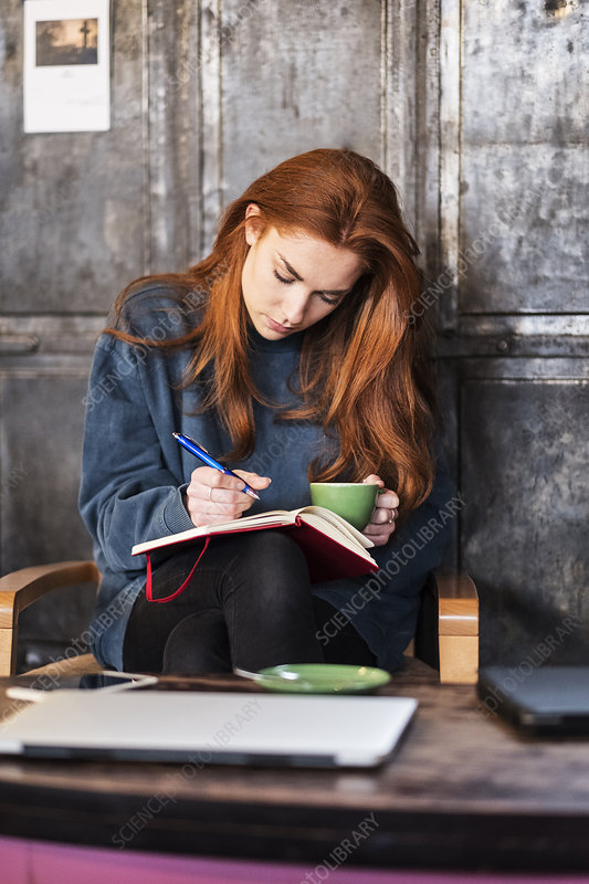 Young woman with a notebook and cup of coffee