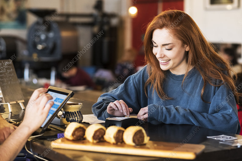 Smiling young woman in a restaurant, paying her bill