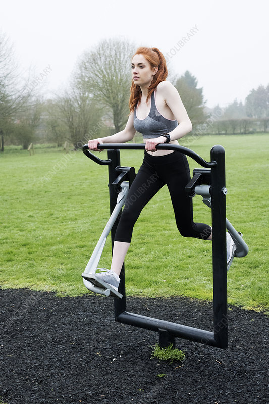 Young woman exercising using outdoor exercise machine