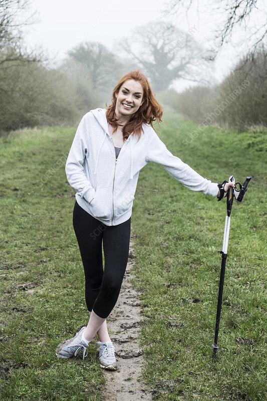 Young woman exercising outdoors, looking at camera