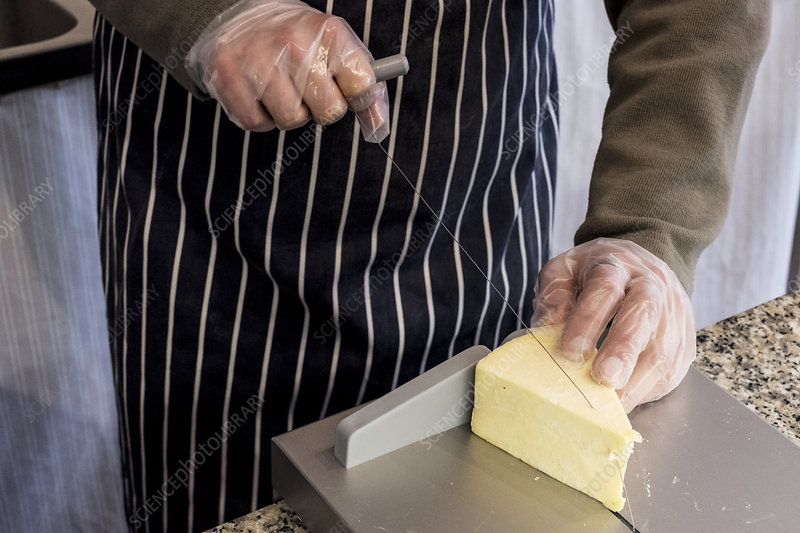 Man in a delicatessen, slicing cheese with wire cutter