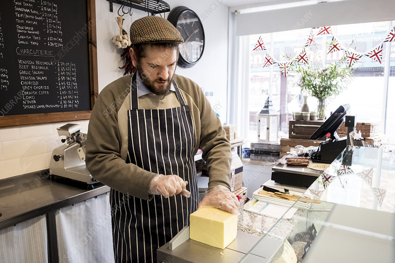 Bearded man at counter in a delicatessen cutting cheese