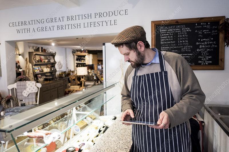 Bearded man in a delicatessen holding digital tablet