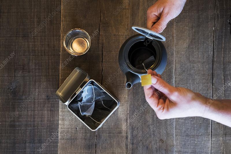 Person adding tea bag to small black tea pot