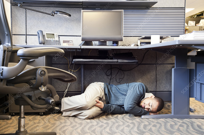Man taking a nap under his desk in a corporate office