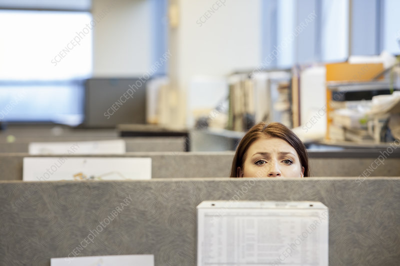 A young woman looking over the top of her office cubicle
