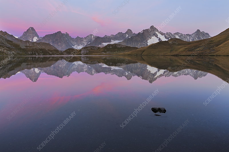 Colourful pink sky at dawn above Fenetre Lake, Swiss Alps